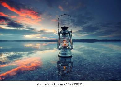 vintage lantern at sunset, romantic evening at the beach