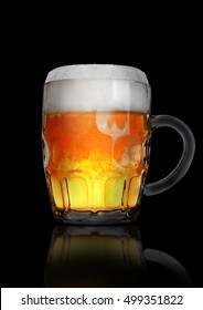 Vintage large glass of beer with foam and bubbles on black background