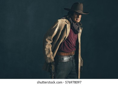 Vintage late 1960s spaghetti western actor. Picking revolver from holster.