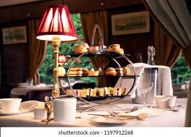 Vintage late afternoon tea stand with sandwiches, cakes and tea as see through the window of a train carriage.