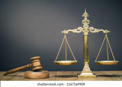 Vintage law scales and wooden gavel on the desk front dark background. Symbols of justice. Retro old style filtered photo