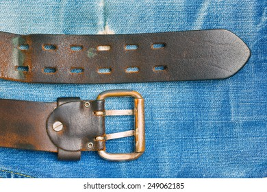 Vintage leather belt with a buckle on the background of denim
