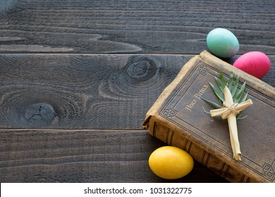 Vintage Leather Bible with grass cross, palm leaves, Colorful Easter Eggs on Dark Rustic Wood Board Background with room or space on side for copy, text, your words or design.  Horizontal flat lay
