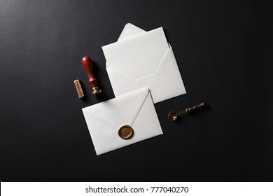 Vintage letter envelope with golden wax seal, stamp, spoon and postcard on black paper background. Mock-up for your design. Flat lay.