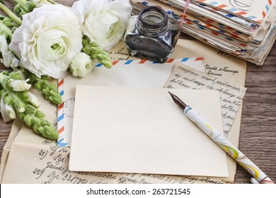Vintage letters, ink and pen. White persian buttercup flowers (ranunculus) on wooden background, copy space
