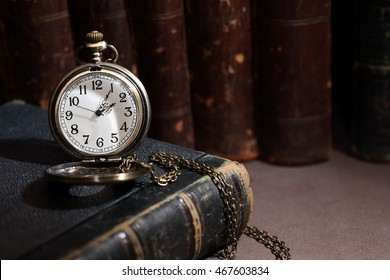Vintage library. Vintage pocket watch near books in a row on dark background