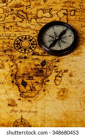 vintage lifestyle concept: retro compass on an antique world map