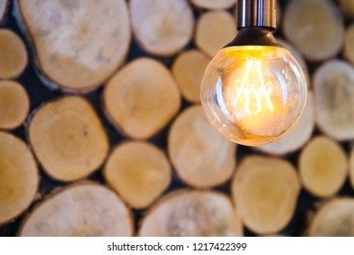 Vintage light bulb on wooden background with bright yellow shining wire,