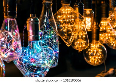 Vintage light glass bulbs with colorful garlands inside hanging in the dark