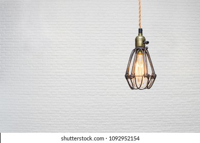 Vintage light hang from ceiling with white brick background