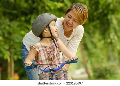 Vintage of little Asian child with mother practice to riding a bicycle