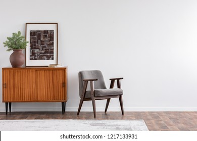 Vintage living room interior with retro furniture and poster on the cabinet, real photo with copy space on the white wall
