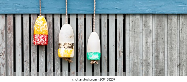 Vintage lobster buoys against a weathered wood fence. Banner format with copy space.