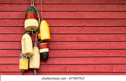 Vintage lobster buoys hanging on rustic red painted exterior wood siding wall. Nautical background with copy space.