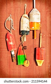 Vintage lobster floats hanging on a wall of faded red wooden planks. Retro color