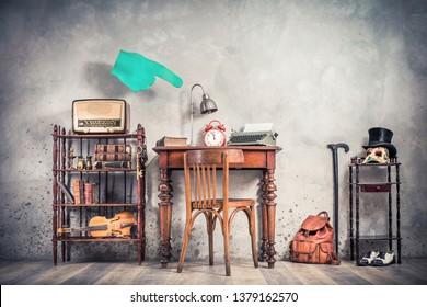 Vintage loft room with antique chair, old typewriter, lamp, clock on oak wooden desk, retro radio, books, fiddle, keys on shelf, mask, cylinder hat, shoes, cane, backpack, conceptual forefinger