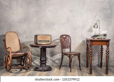 Vintage loft room with antique rocking chair, broadcast radio, old typewriter and lamp on oak wooden desk front concrete wall background with shadows. Retro style filtered photo