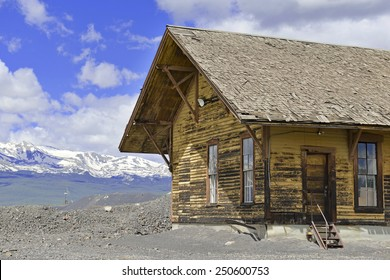 Vintage log cabin in mining town with mountain background, Rocky Mountains, Colorado