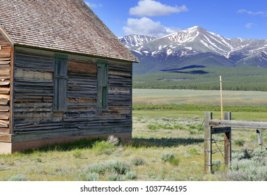 Vintage log cabin in pasture in the Rocky Mountains with alpine background