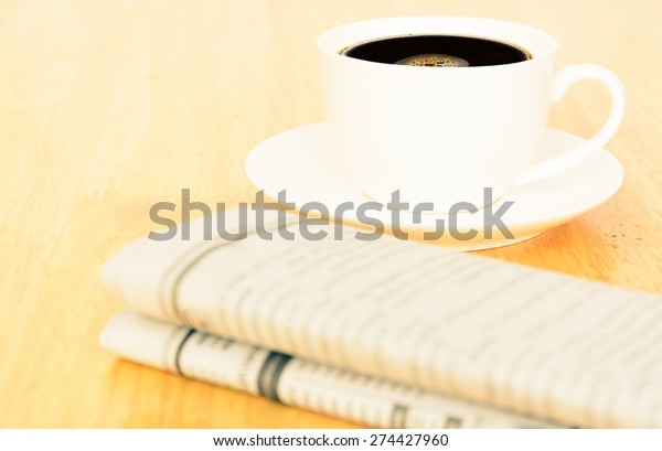 Vintage look of coffee and newspaper on wooden table