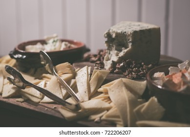 Vintage look image of cheese plate served with various types of cheese in a restaurant