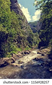 Vintage look of mountain river in the forest and mountain peaks in Turda gorge, Romania