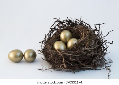 A vintage look for an old, bird's nest sitting on a white cloth background with five bright, golden eggs. For Easter, money savings, or other ideas. A simple horizontal format with copy space room.