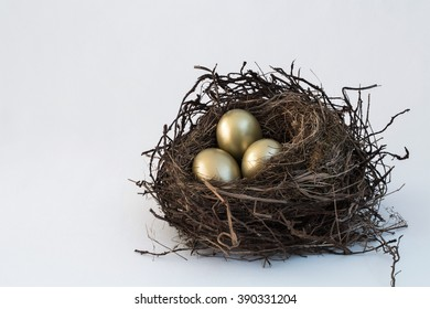 A vintage look for an old, bird's nest sitting on a white cloth background with three bright, golden eggs. For Easter, money savings, or other ideas. A simple horizontal format with copy space room.