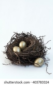 A vintage look for an old, bird's nest sitting on a white cloth background with three bright, golden eggs. For Easter, money savings, or other ideas. A simple vertical format with copy space room.