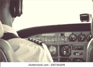 Vintage look photograph of a pilot in uniform in a cockpit with black and white elements traveling trough the sky on his way to the end of the world.