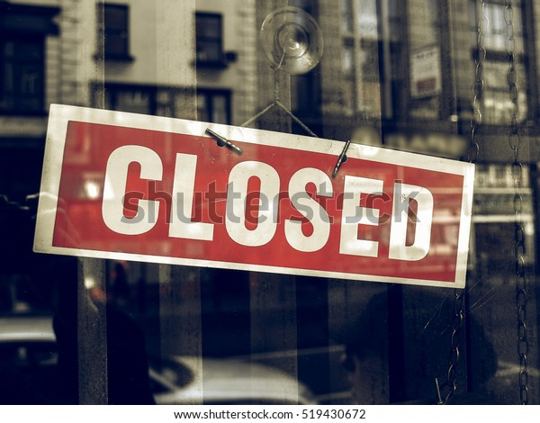 Vintage looking Closed sign in a shop showroom with reflections