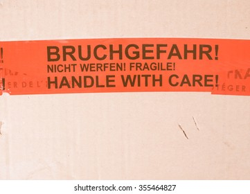 Vintage looking Fragile packet parcel with warning label in English and German - Handle with care, Bruchgefahr