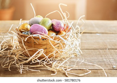 Vintage looking image of Easter eggs in a woven basket over wooden background. Color toning, retro effect filters