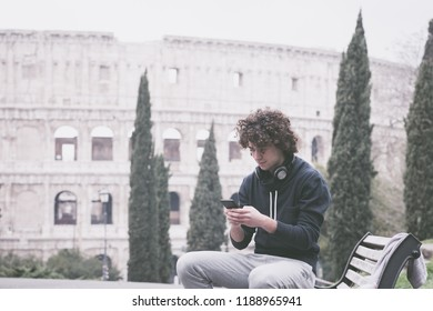 Vintage looking image of handsome young man in sports cloths using his mobile phone in Rome with Colosseum in the background