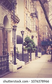 Vintage looking New York City Manhattan street scene from sidewalk with pretty apartment building with railing and lamp post.