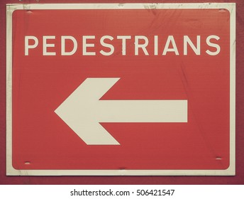 Vintage looking Pedestrians direction sign in white over red background