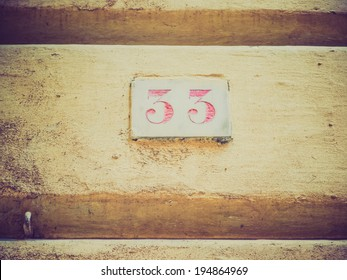 Vintage looking A red 33 house number in Genoa where there are two series of house numbers, red and blue