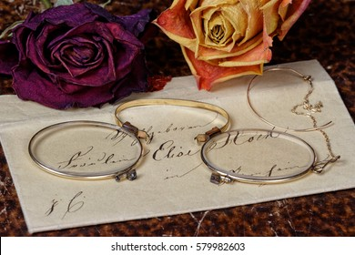 Vintage Love Letter Reading: closeup of a vintage envelope from the early 19th century on  old book cover background with historic female glasses and dried roses lying on it