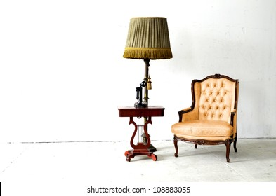 vintage luxury armchair and old day telephone in white room