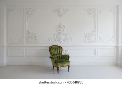 vintage luxury green armchair in white room over wall design bas-relief stucco mouldings roccoco elements