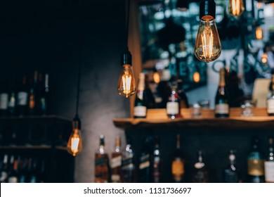 Vintage luxury interior lighting decor in cafe. old Vintage light bulb lamps. Restaurant Bar lighting interior design. Vintage Light bulbs at wine chamber in front of alcoholic drinks bottles
