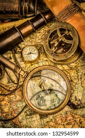 Vintage magnifying glass, compass, telescope and a pocket watch lying on an old map.