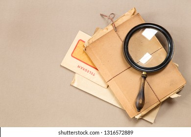 Vintage magnifying glass with an old telegram and books