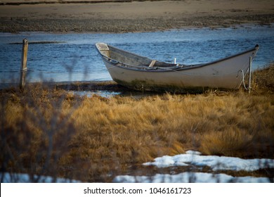 A vintage Maine dory boat moored to a wooden post along the shoreline in a salt marsh in Ogunquit, Maine.