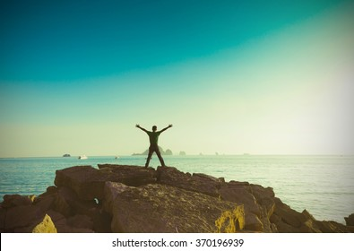 Vintage Man enjoying view nature in sea. Outstretched arms fresh morning air summer