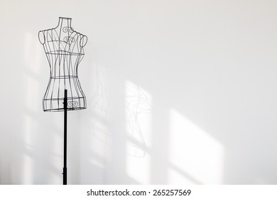 Vintage mannequin stand at white wall.