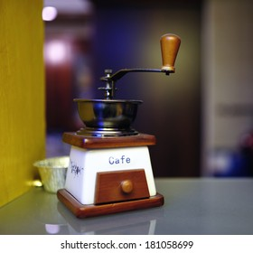Vintage manual coffee mill on glass table