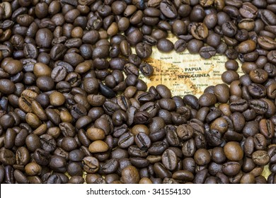 Vintage map of Papua New Guinea covered by a background of roasted coffee beans. This nation is one of the main producers and exporters of coffee. Horizontal image.