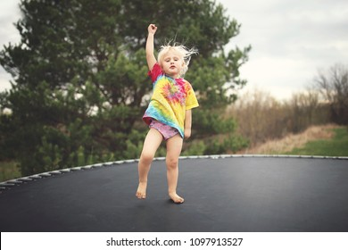 A Vintage Matte style photo of a little toddler girl jumping on her trampoline outside on a summer day.