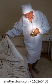 Vintage mature man going to bed with a candle in the dark